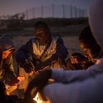 Jóvenes intentando calentarse con una hoguera. Al fondo, el centro de estancia temporal de inmigrantes y la valla de Melilla (España) , 11–04–2014. | SANTI PALACIOS